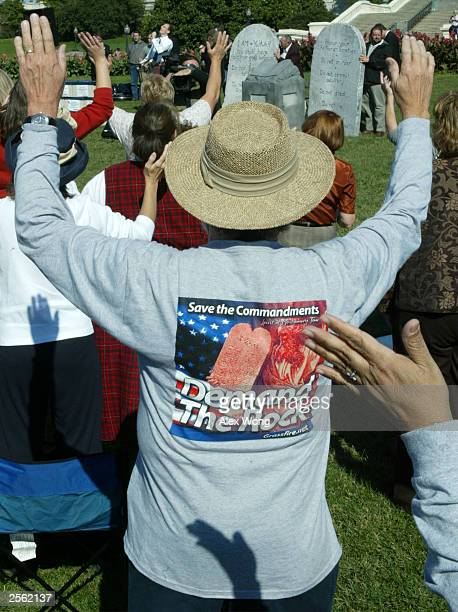People pray in front of a display of a representation of the Ten Commandments October 5 2003 during a rally at the West Lawn of the US Capitol in...