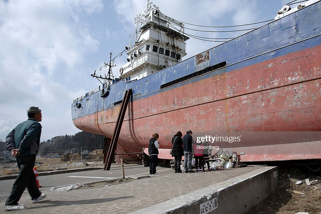 People pray in front of a vessel swept inland by the tsunami    News