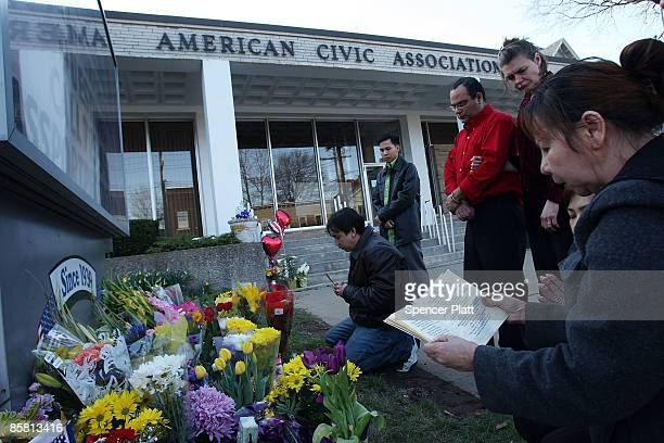 People pray in front of the American Civil Association to pay their respects to the 13 victims of a recent mass shooting April 5, 2009 in Binghamton,...