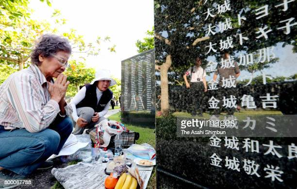 People pray in front of the Cornerstone of Peace where the names of their bereaved family members and relatives engraved at the Peace Memorial Park...