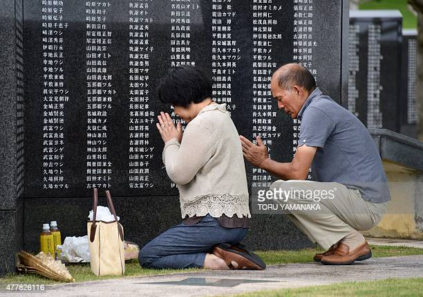 People pray in front of the monument commemorating those who died in the battle of Okinawa during World War II at the Peace Memorial Park in Itoman...