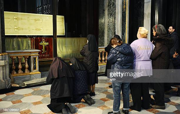 People pray in front of 'The Shroud of Turin' on March 30 2013 in the Turin cathedral On Holy Saturday the linen cloth imprinted with the faint...