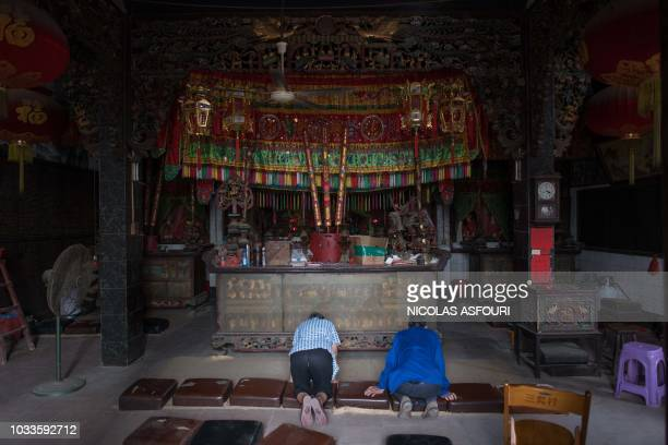People pray inside of a temple ahead of the arrival of the Super Typhoon Mangkhut in Sanhe village on the outskirts of Zhanjiang in Guangdong...