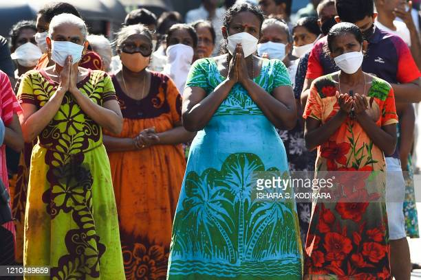 People pray near the St. Anthonys church on the first anniversary of the Easter Sunday attacks in Colombo on April 21, 2020. - Survivors of...