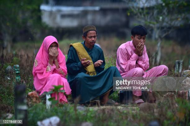 People pray next to the grave of relatives at a cemetery during the Islamic Eid alAdha festival in Thailand's southern province of Narathiwat on July...