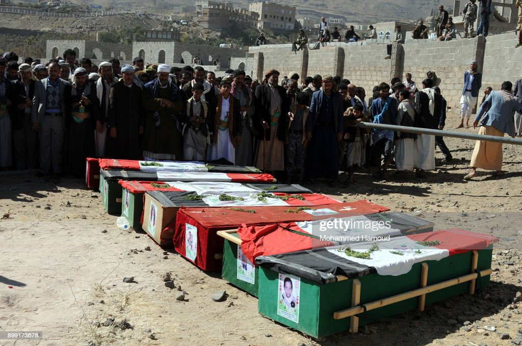 People pray on coffins of members from one family after they were killed by airstrikes carried out by the Saudi-led coalition hit their house on Monday leaving the nine members including five children killed on December 26, 2017 in Sana'a, Yemen. The Houthi-run Saba news agency reported that at least 71 civilians, including 11 children, were killed in Yemen in 51 airstrikes carried out by the Saudi Arabia-led military coalition across the country over a 48-hour period.