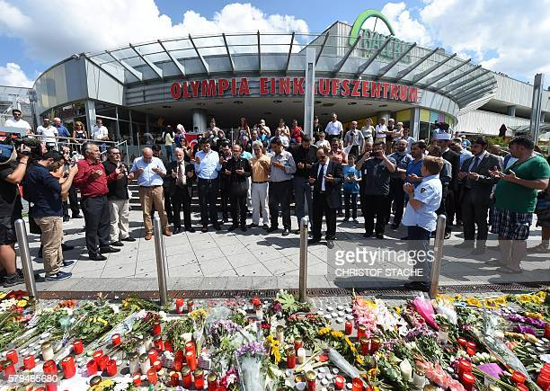 TOPSHOT People pray on July 24 2016 at a memorial of candles and flowers in front of the Olympia Einkaufszentrum shopping centre in Munich southern...