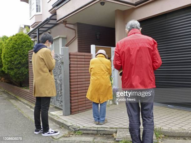 People pray on March 30 in front of the home of veteran Japanese comedian Ken Shimura who died of pneumonia caused by the novel coronavirus the...