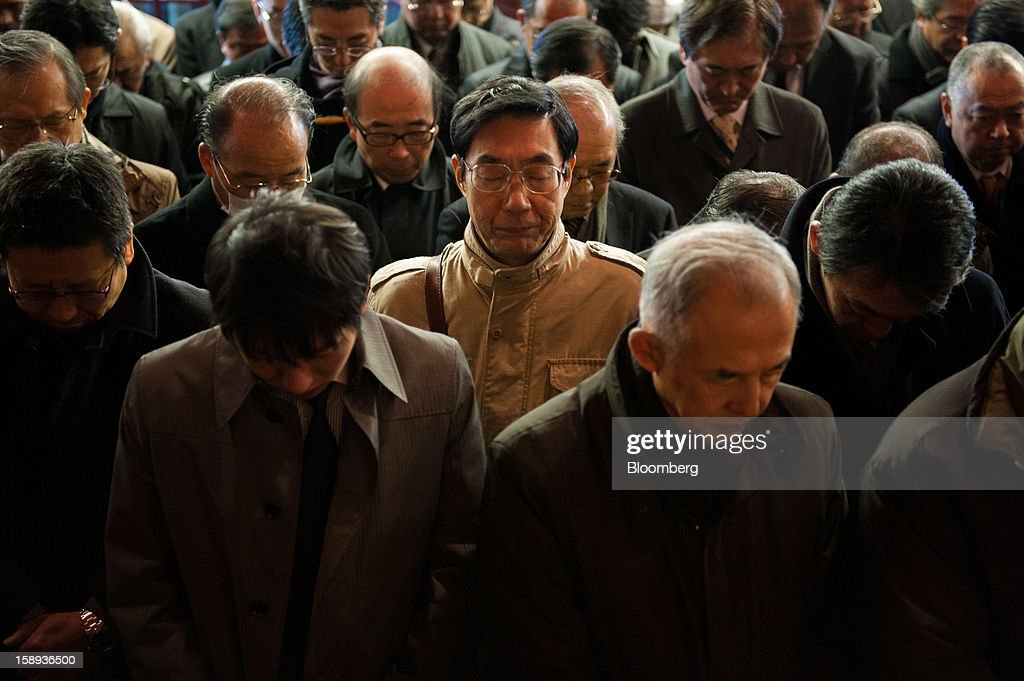 People pray on the first day of business in 2013 at the Kanda Myojin shrine in Tokyo, Japan, on Friday, Jan. 4, 2013. Japan's deflation-plagued economy has contracted 7 percent since 2007 as six prime ministers, including Shinzo Abe in his first term, failed to reverse the course. Photographer: Noriko Hayashi/Bloomberg via Getty Images