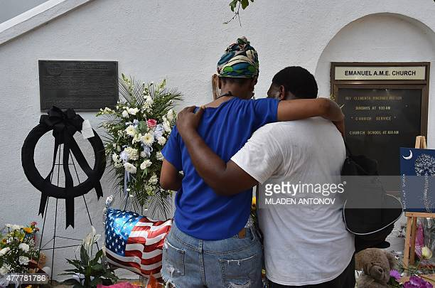 People pray outside Emanuel AME Church in Charleston, South Carolina, on June 19, 2015. Police captured the white suspect in a gun massacre at one of...