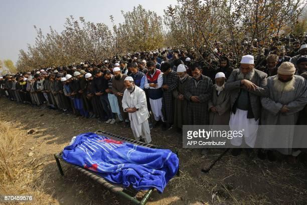 People pray over the body of Indian slain policeman Abdul Salam Khan at Kareva Shadab village in Shopian some 55 km of south of Srinagar on November...