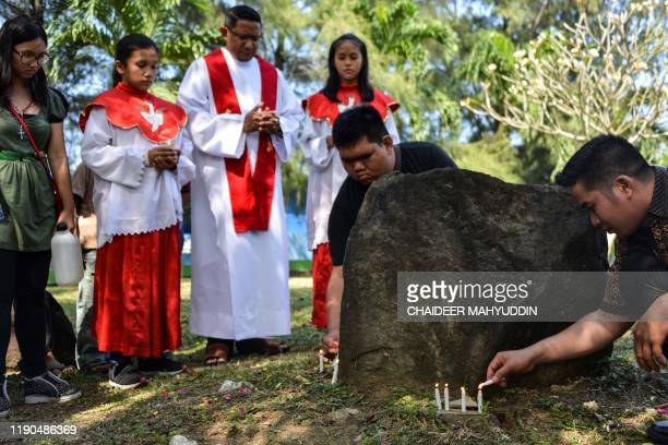 People pray to mark the 15th anniversary when an earthquake and resulting tsunami killed at least 170000 people in the country and thousands of...