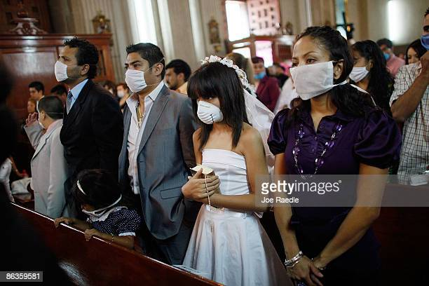 People pray together as some wear surgical masks to help prevent catching the swine flu during a church service on May 3 2009 in Mexico City Mexico...