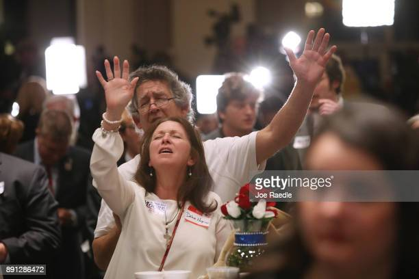 People pray together as they attend the election night party for Republican Senatorial candidate Roy Moore as he runs against his Democratic opponent...