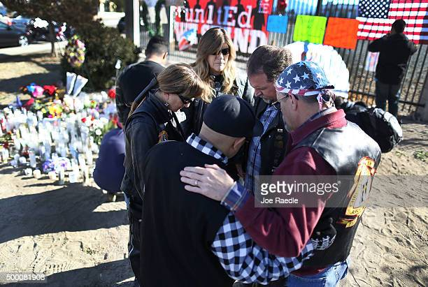 People pray together as they pay their respects at a memorial near the Inland Regional Center on December 5 2015 in San Bernardino California Police...