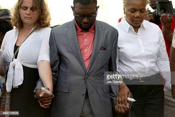 People pray together during a vigil in front of the North Charleston City Hall for Walter Scott on April 10 2015 in North Charleston South Carolina...