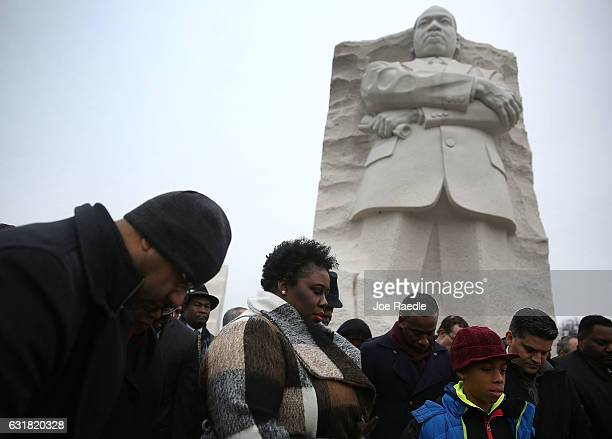 People pray together in front of the Martin Luther King Jr memorial on the day that honors him on January 16 2017 in Washington DC Martin Luther King...