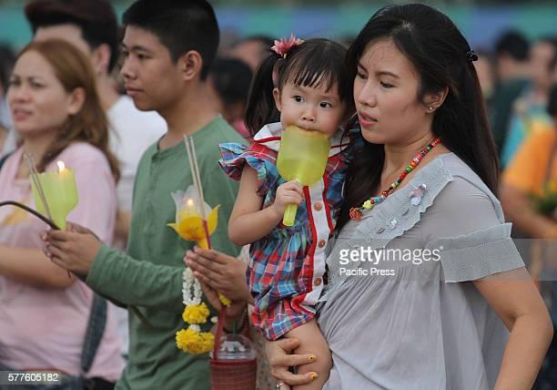 People pray while holding candles as they walk around the Phra Si Sakkaya Thotsaphala Yan Prathan Phutthamonthon Suthat during Asalha Puja Day at...