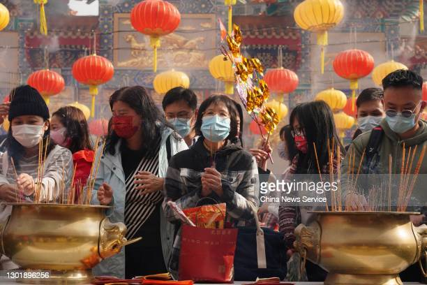 People pray with incense sticks at Wong Tai Sin Temple on the first day of the Chinese New Year, the Year of the Ox, on February 12, 2021 in Hong...