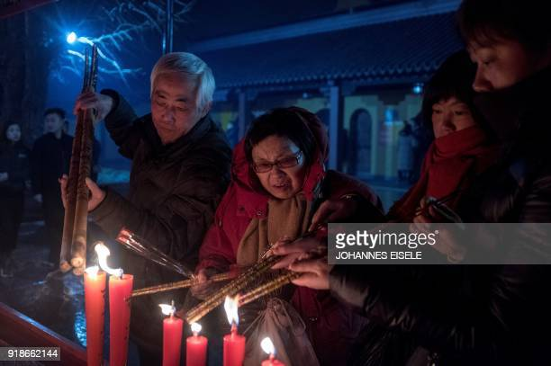 People pray with incense sticks to celebrate the Lunar New Year marking the Year of the Dog at the Longhua temple in Shanghai early February 16 2018...