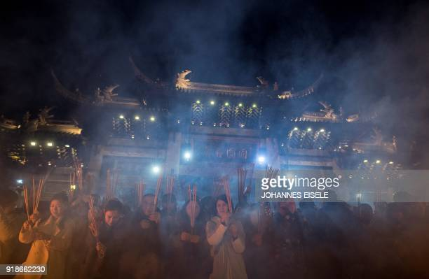 TOPSHOT People pray with incense sticks to celebrate the Lunar New Year marking the Year of the Dog at the Longhua temple in Shanghai early February...