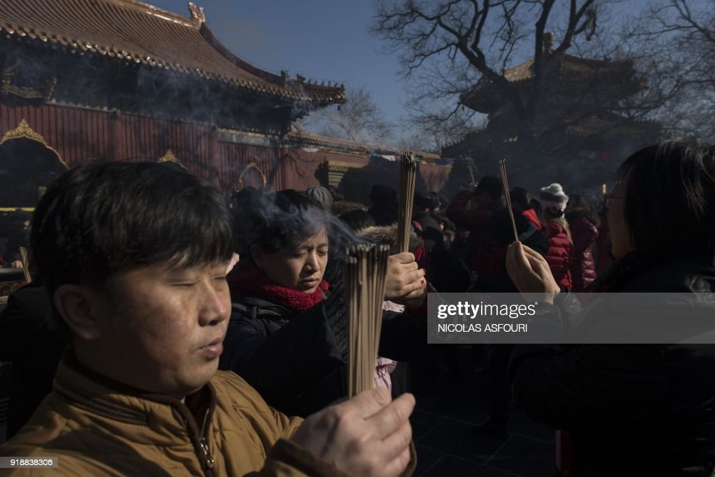 People pray with incense sticks to celebrate the Lunar New Year, marking the Year of the Dog, at the Lama temple in Beijing on February 16, 2018. The Lunar New Year fell on February 16 this year, with celebrations in China scheduled to last for a week. /