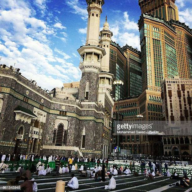 people praying at al-haram mosque against makkah clock royal tower hotel - al haram mosque stock photos and pictures