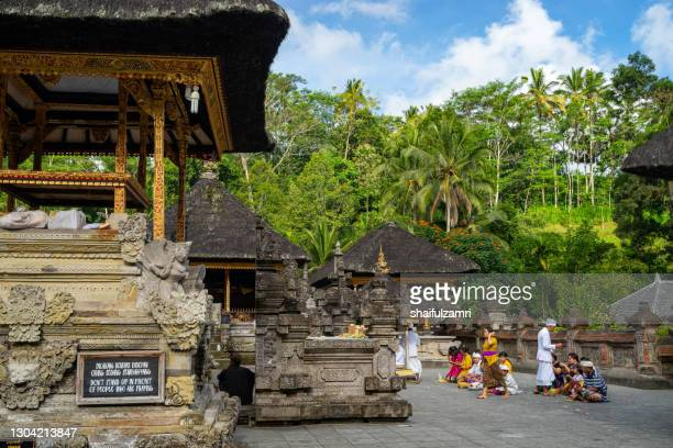 people praying at holy spring water temple puru tirtha empul, bali, indonesia. - shaifulzamri stock-fotos und bilder