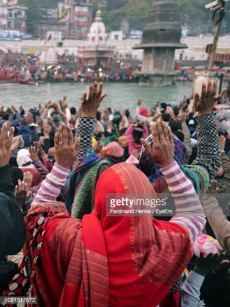 people praying at riverbank in city - worshipper stock pictures, royalty-free photos & images