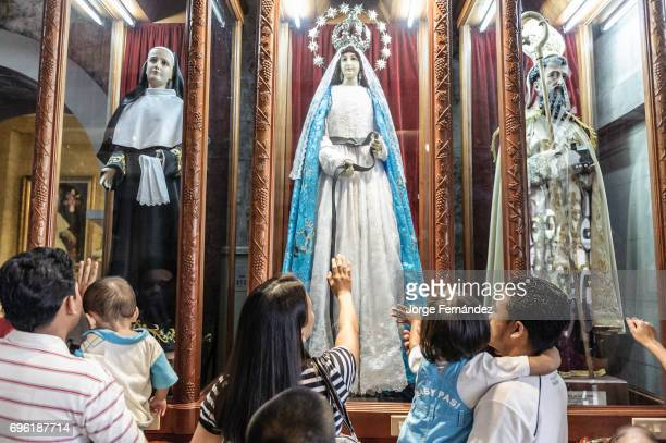 People praying in front of an statue of The Virgin Mary inside The Basilica Minore del Santo Niño.