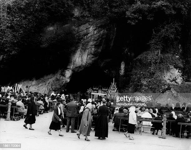 People praying in front of the Grotto of Massabielle during the centenary of the apparitions of Our Lady to Saint Bernadette Soubirous Lourdes...