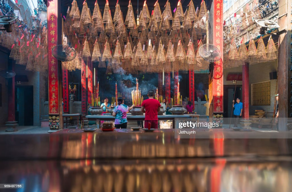 People praying Inside Thien Hau Pagoda Cholon, Ho Chi Minh City. Pagoda for the Cantonese Congregation. Incense burning on the central table with incense prayers above. : Stock-Foto