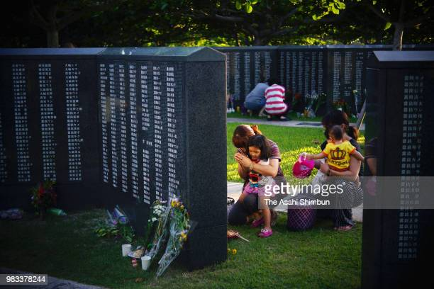 People prays in front of the Cornerstone of Peace where the names of their bereaved family members and relatives engraved at the Peace Memorial Park...