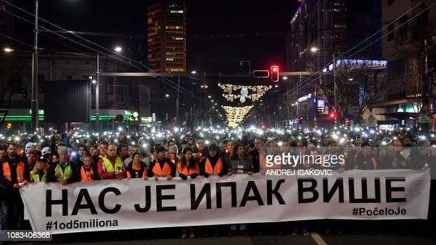 People preceding thousands ones hold a banner reading in cyrillic Still there is more of us during a silent march in Belgrade in memory of Serb...