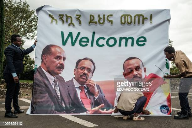 People prepare a banner showing portraits of Eritrea's President Isaias Afwerki Somalia's President Mohamed Abdullahi Mohamed and Ethiopia's Prime...