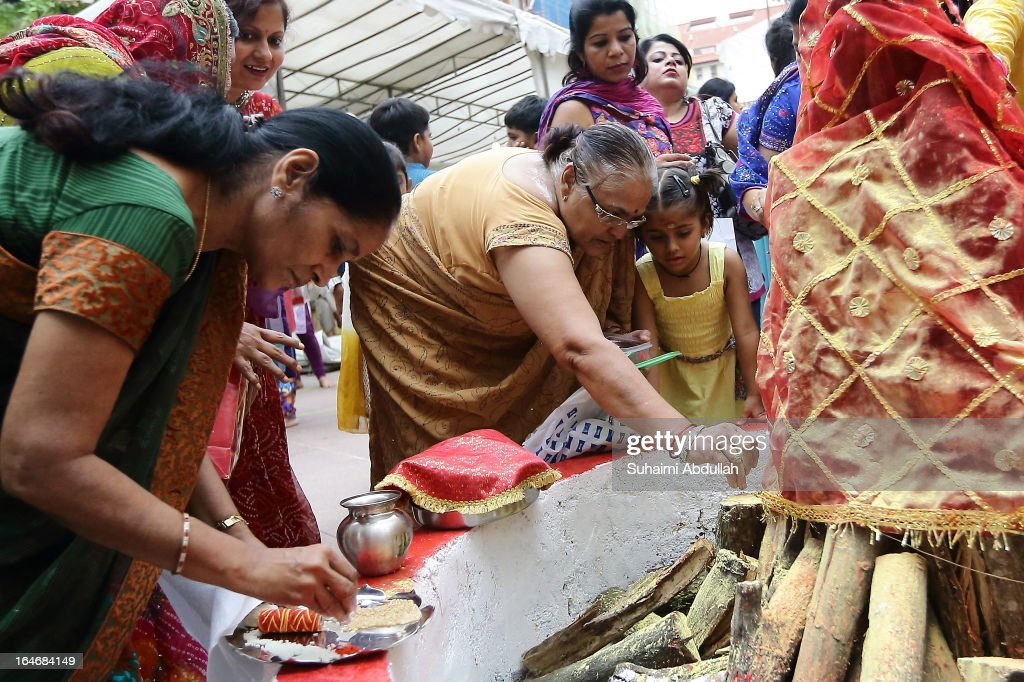 People prepare a bonfire and give offerings as they prepare to celebrate Holika Dahan on March 26, 2013 in Singapore. Holika Dahan, or burning of demon Holika, is celebrated the night before the Holi festival and is said to commemorate the escape of Prahlad, adevotee of god Vishnu, from being burned when carried by Demoness Holika into a fire. The bonfire is said to epitomize the victory of good over evil.