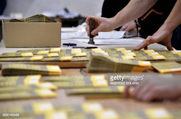 People prepare ballots at a polling station in downtown Rome on March 3, 2018. - Italians vote on March 4 in one of the country's most uncertain...