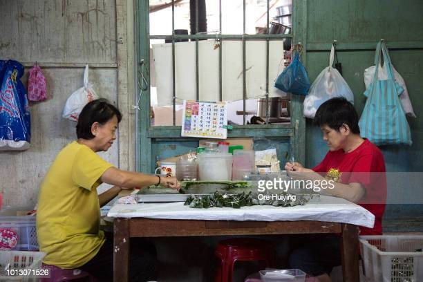 People prepare homemade traditional snacks for sale from a house in a village in Air Itam that forms part of the 234 acre land acquired by the 1MDB...