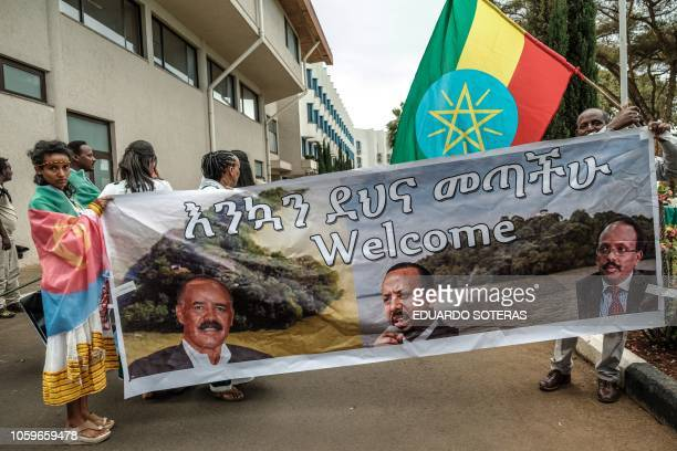 People prepare the banner showing portraits of Eritrea's President Isaias Afwerki Somalia's President Mohamed Abdullahi Mohamed and Ethiopia's Prime...