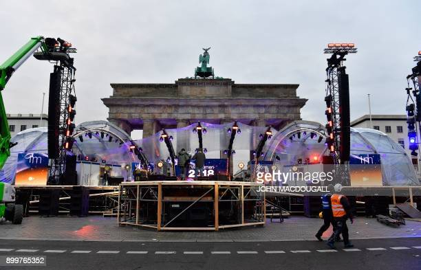 People prepare the stage for New Year's Eve festivities in front of Berlin's landmark Brandenburg Gate on December 30 2017 / AFP PHOTO / John...