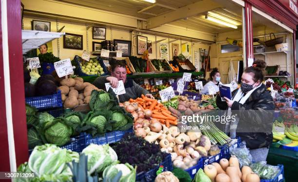 People prepare their fruit and veg market stall at Stockport Market on March 12, 2021 in Stockport, England.
