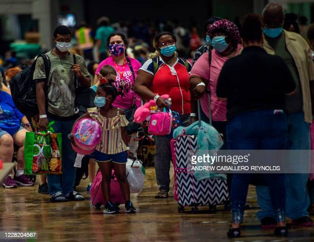 People prepare to board a bus for evacuation before the arrival of hurricane Laura in Lake Charles, Louisiana on August 25, 2020. - Storm Laura was...