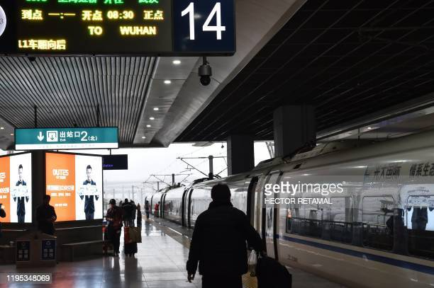 People prepare to board a train in the direction of Wuhan City at Hongqioa train station as they head home for the Lunar New Year in Shanghai on...