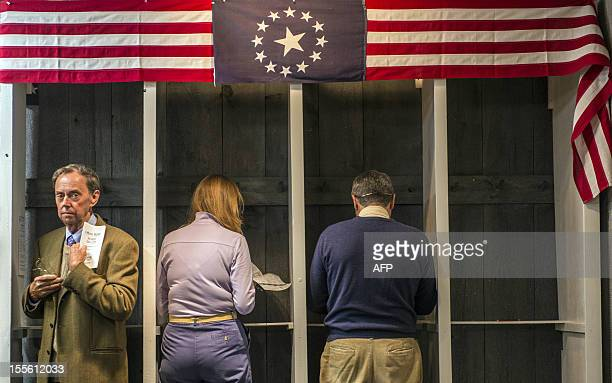 People prepare to cast their ballots inside a polling station just after midnight on November 6 2012 in Dixville Notch New hampshire the very first...