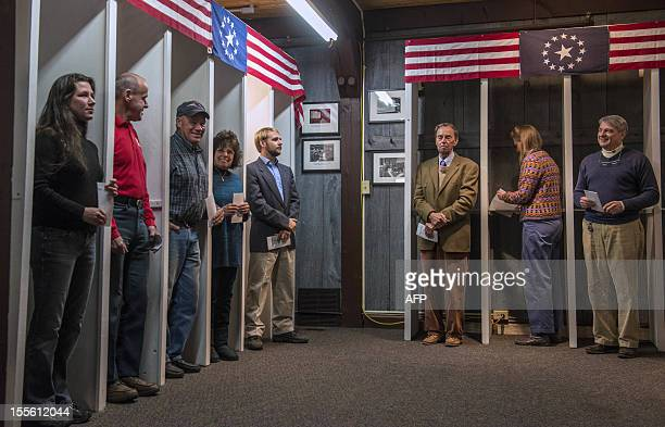 People prepare to cast their ballots inside polling booths just after midnight on November 6 2012 in Dixville Notch New hampshire the very first...