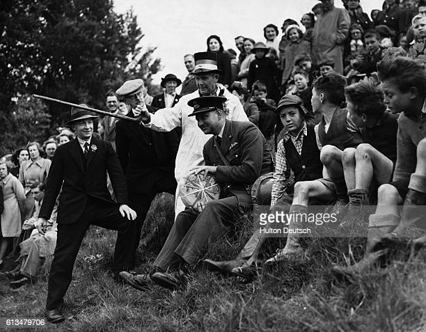 People prepare to chase a cheese down the side of a hill in Gloucester