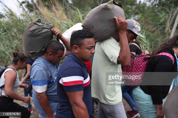 People prepare to cross through the low waters of the Táchira River near the Simón Bolívar international bridge which connects Cúcuta with the...