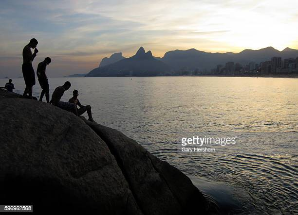 People prepare to dive into the Atlantic Ccean from the rocks on Arpoador at Ipanema Beach at sunset in Rio de Janeiro Brazil June 7 2014