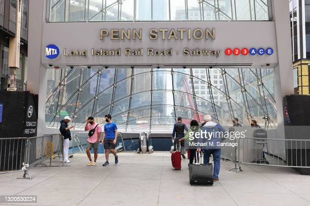 People prepare to enter Penn Station ahead of the Memorial Day weekend in Midtown Manhattan on May 28, 2021 in New York City. Travel for Memorial Day...