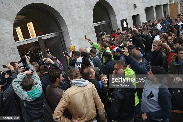 People prepare to enter the Apple Store at 8am on the first day of sales of the new Apple iPhone 6 in Germany on September 19 2014 in Berlin Germany...